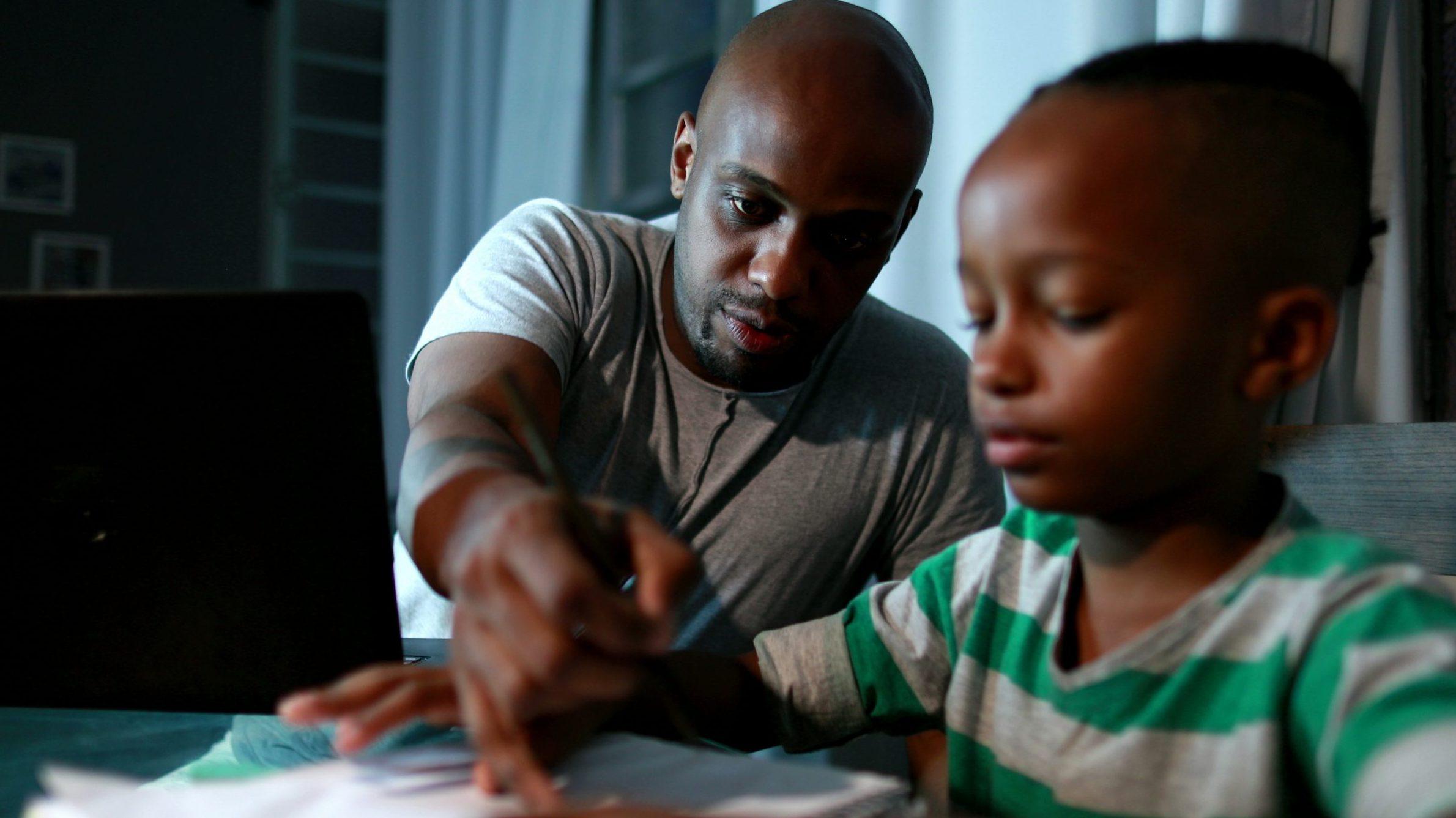 Vader helpt zoon bij huiswerk